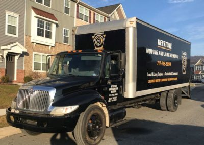 Keystone Moving And Junk Removal's moving truck outside a residential area