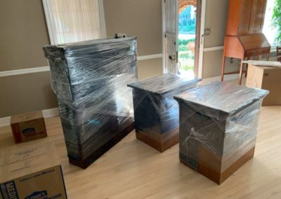 Pieces of furnitures wrapped in plastic sitting inside a living room area ready for moving.