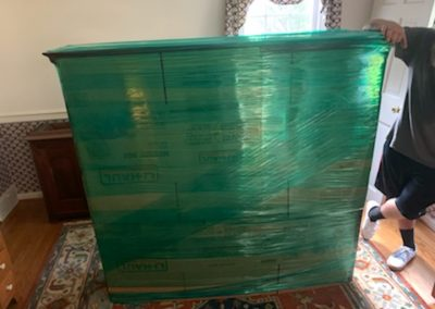 Image: a large piece of furniture professionally wrapped by Keystone Moving.
